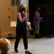 A woman teaches students in a dance studio.