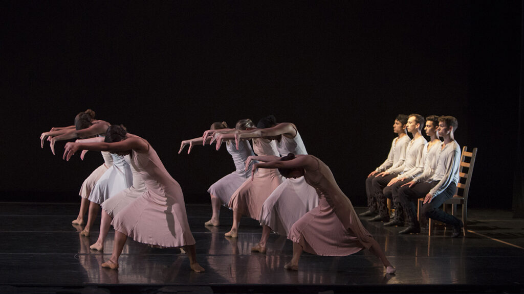Dancers wearing dresses lean forward with arms out while other dancers wearing white shirts and black pants sit on chairs