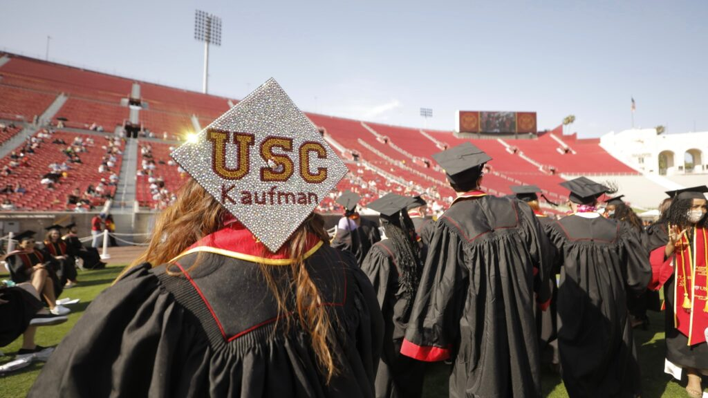 A woman sits in a stadium wearing a graduation gown and cap.