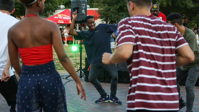 one person dances as four people stand in a circle around him