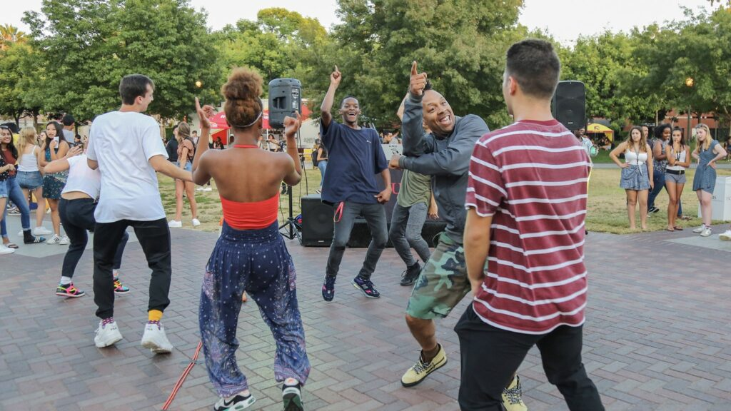 a group of people stand in a circle dancing