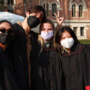 four students in black convocation robes pose for a picture. They are all wearing masks