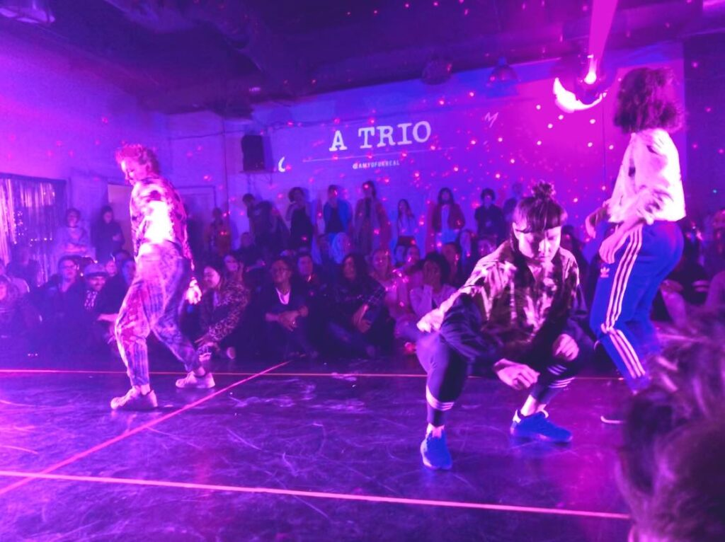 three people dancing with an audience sitting and watching them. Two of the dancers are standing, one is squatting.