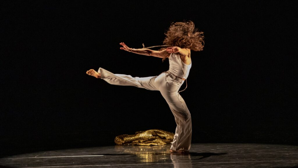 woman dressed in all white dancing alone onstage with her back leg extended